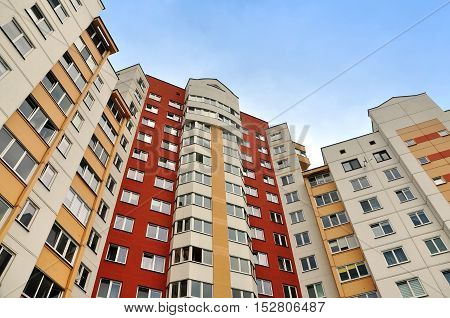 Grodno, Belarus - August 8, 2016: Facade of a modern multistory residential building of red yellow and white color. Look up. Grodno, Belarus.