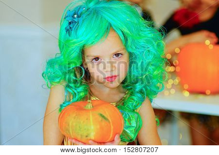 Little mermaid with a pumpkin during Halloween party