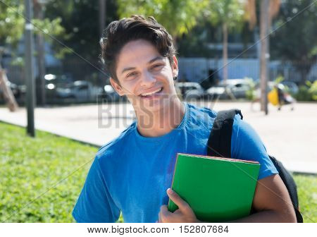 Laughing caucasian male student outdoor in the city in the summer