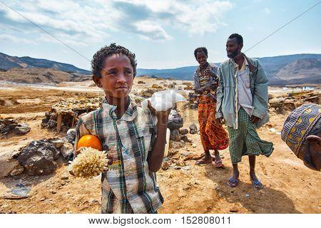 LAKE ASSALDJIBOUTI-FEBRUARY 06 2013:Boy sells salt crystals on the shore of Lake Assal