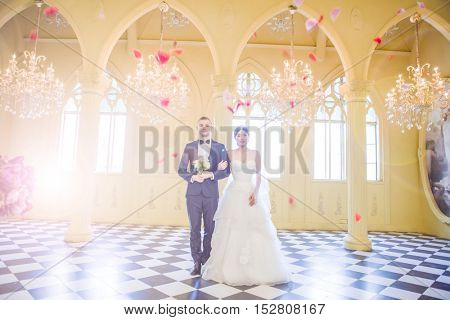 Full length of elegant wedding couple holding hands in church