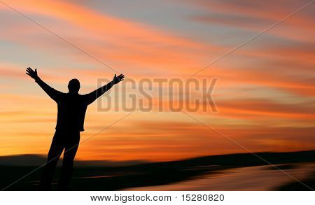 Man with outstretched arms facing a beautiful sunset.