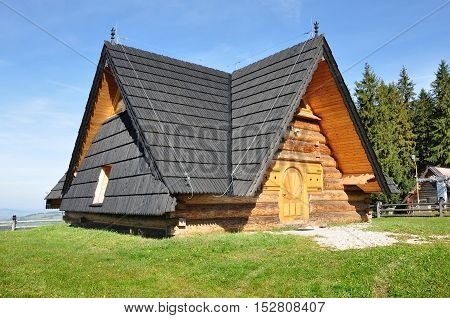 Zakopane, Poland - October 9, 2014: Residential wooden house with high pitched roof in the style of Zakopane in the background of a mountain landscape.