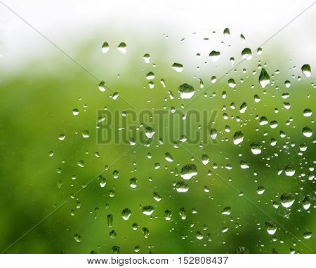 Abstract blur green natural background with glass and rain drops in the foreground.