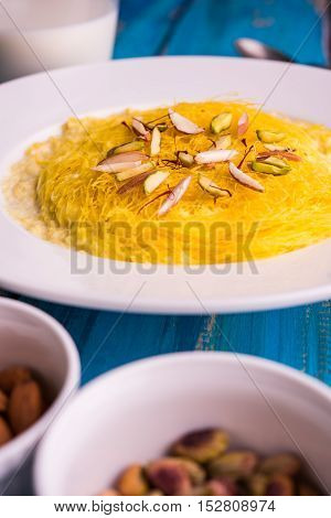 Indian sweet kesar sutarfeni or sutar feni or firni or seviyan or laccha, shredded, flaky-rice-flour roasted in ghee, blended with melted sugar to form a cotton candy, with pistachio and almonds