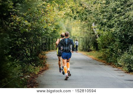 two athletes runners running down road in autumn Park with fallen yellow leaves