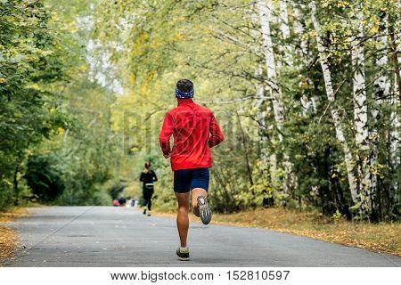 male marathon runner running on road in autumn Park with fallen yellow leaves