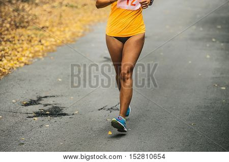 girl runner is running marathon on road in autumn forest with yellow leaves
