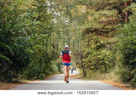 male athlete runner running on an asphalt road in autumn forest fallen yellow leaves
