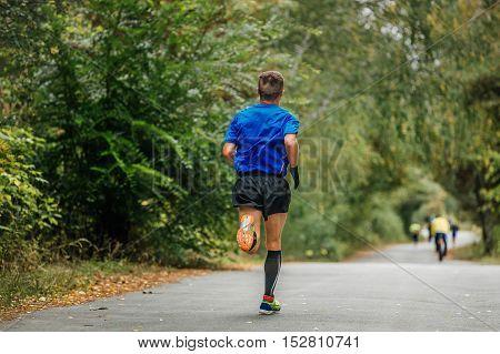 male athlete runner running in autumn Park marathon