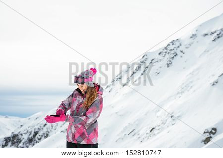 Young and beautiful skier putting the gloves on.