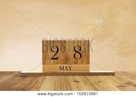 Cube shape calendar for May 28 on wooden surface with empty space for text.