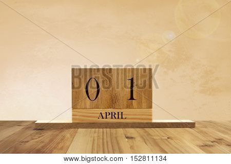 Cube shape calendar for April 01 on wooden surface with empty space for text.