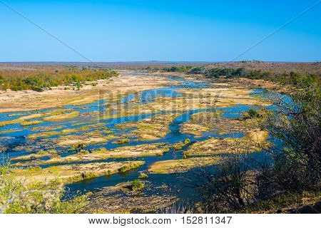 Olifants river scenic and colorful landscape with wildlife in the Kruger National Park famous travel destination in South Africa. Clear blue sky.