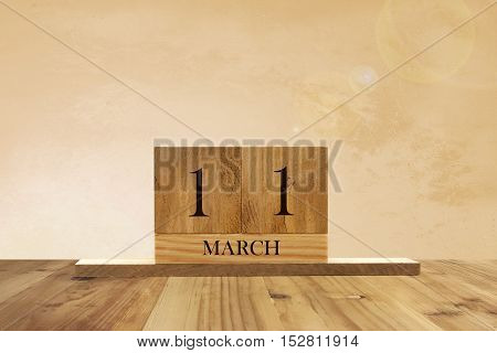 Cube shape calendar for March 11 on wooden surface with empty space for text.