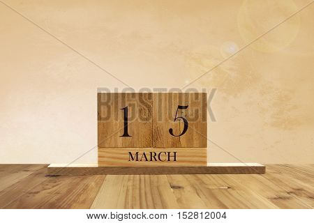 Cube shape calendar for March 15 on wooden surface with empty space for text.
