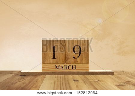 Cube shape calendar for March 19 on wooden surface with empty space for text.
