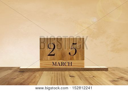 Cube shape calendar for March 25 on wooden surface with empty space for text.