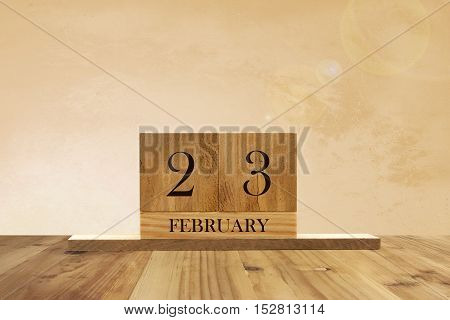 Cube shape calendar for February 23 on wooden surface with empty space for text.