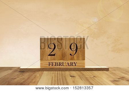 Cube shape calendar for February 29 on wooden surface with empty space for text.