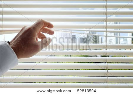 close up view of man's head spreading blinds and sunny city background