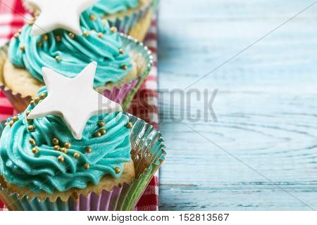 Christmas cupcakes decorated with a sweet mastic on the wooden table