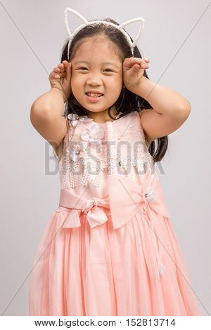 Child With Cat Ear Headband In Pink Dress, Isolated On White