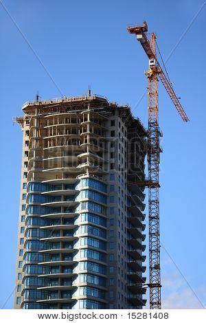 Sitio de la construcción del rascacielos con la grúa contra un cielo azul brillante.