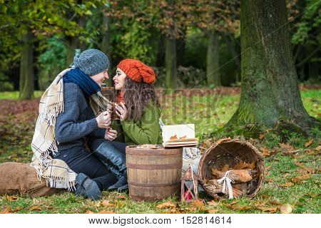 Happy romantic couple at fall drinking coffee in autumn garden