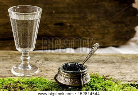 Black caviar. Silver vase caviar. Vintage shot glass. Vodka. The old Board and moss. Vintage style.