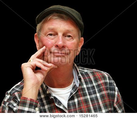 Handsome wise retired gentleman, casually dressed in a pageboy cap and plaid shirt.