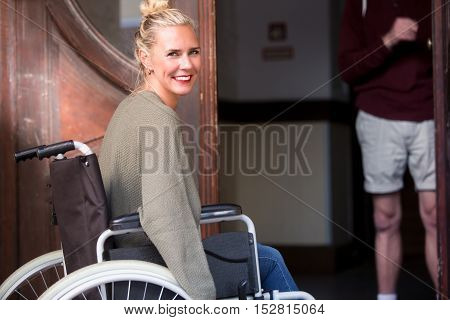 blond woman in wheelchair in front of entrance and man holding the door