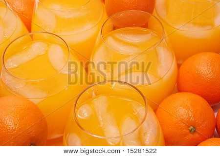 Glasses of freshly squeezed orange juice and oranges.