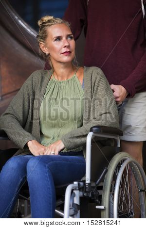 woman in wheelchair in front of entrance with a friend