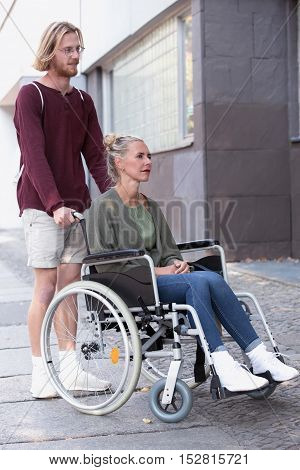 woman in wheelchair on the sidewalk and young man helping her