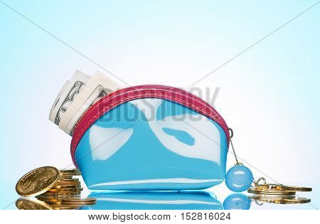 close up view of blue purse filled with cash on color back