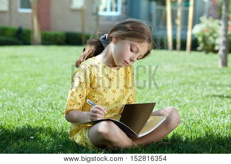 portrait of little girl studying on the grass in summer environment