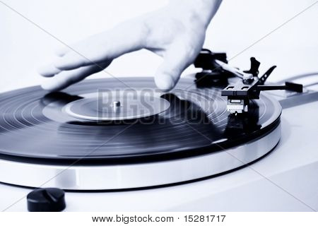 Dj mixing a spinning record. Focus on the needle head.