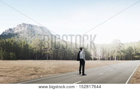 Elegant businessman on road standing with back and looking ahead