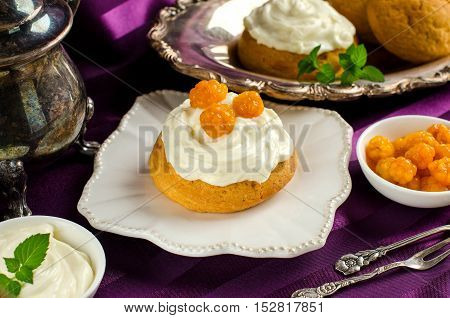 Cream cakes. Yellow cloudberries. Mint leaves. The desserts on the plate. Cloudberries and cream in bowls. Dessert fork and spoon. Purple background. Silverware.