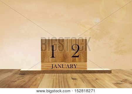 Cube shape calendar for January 12 on wooden surface with empty space for text.