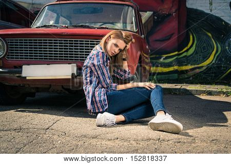 Young attractive model is sitting near the car