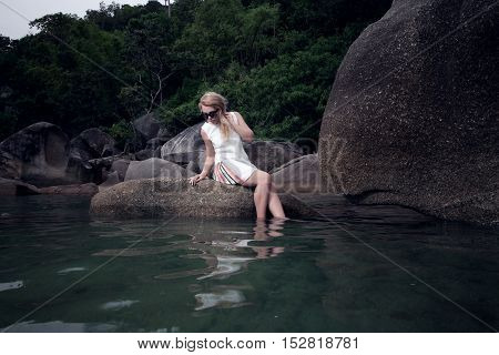 portrait of girl sitting on rock and looking on water