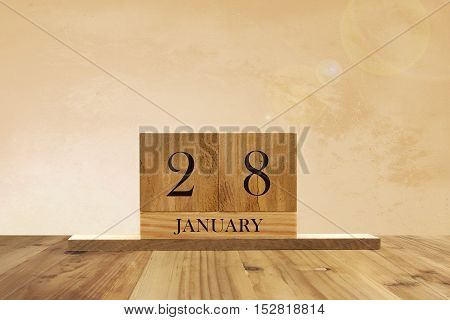 Cube shape calendar for January 28 on wooden surface with empty space for text.