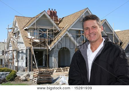 Friendly builder in front of home under construction.