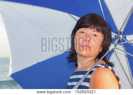 Brunette middle-aged woman on the beach in a beautiful dress with striped umbrella