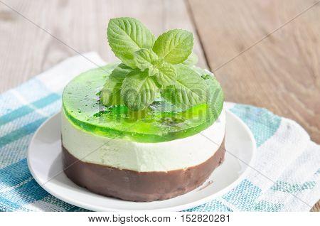 green mint sponge cake on wooden background.