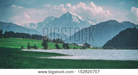 Beautiful view of the lake Muta (Haidersee) and Ortler peak, located near the village St. Valentin, Alps, Italy, Europe, toned like Instagram filter