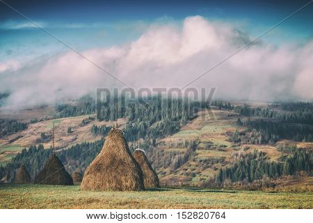 Amazing rural scene on autumn valley. Wooden fence and haystack on a foreground. Carpathians, Ukraine, Europe, toned like Instagram filter