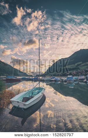 Amazing view of the Lungerersee lake with yachts in the morning mist. Lungern village, Switzerland, Europe, toned like Instagram filter